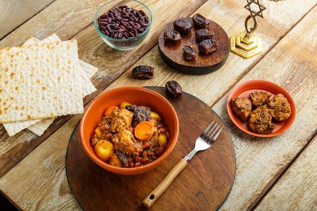 Navette de plat juif avec de la viande dans un plat sur une table en bois près du matzo et des ingrédients.