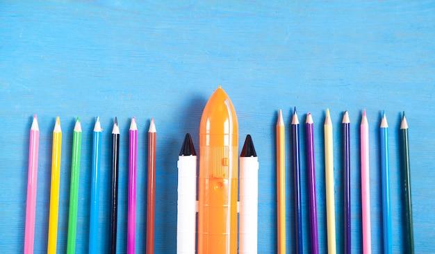 Navette spatiale jouet et crayons de couleur sur fond bleu