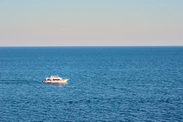 Navire blanc en mer ou océan contre le coucher du soleil