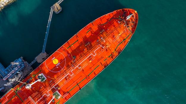 Navire-citerne rouge chargeant et déchargeant du pétrole et du gaz dans un port industriel