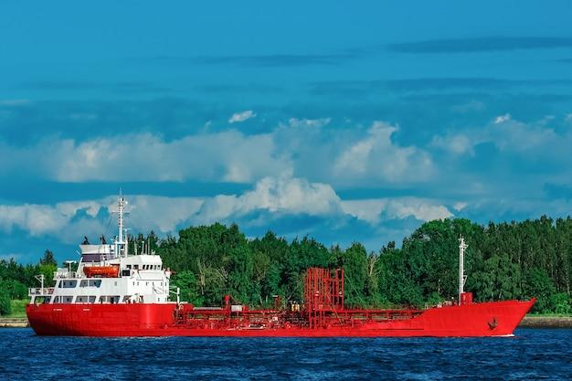 Navire-citerne rouge se déplaçant au bord de la rivière