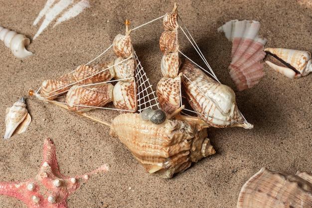 Un navire fait de coquillages se trouve sur le sable parmi les coquillages et une étoile de mer