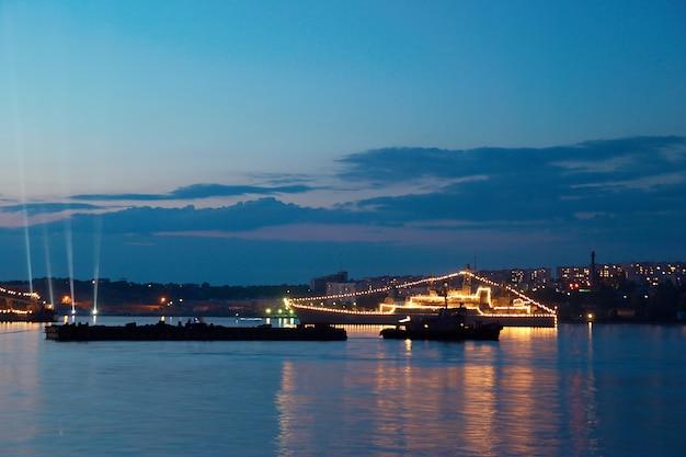 Navire de guerre illuminé dans la baie du soir