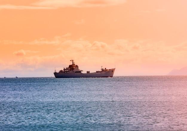 Le navire militaire sur l'océan au lever du soleil