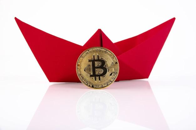Navire en papier rouge, bitcoin doré isolé sur fond blanc