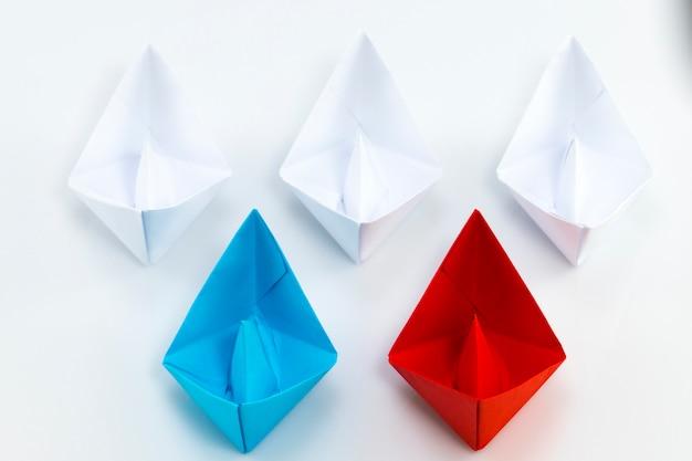 Navire de papier rouge et navire de papier bleu en tête parmi les navires de papier blanc