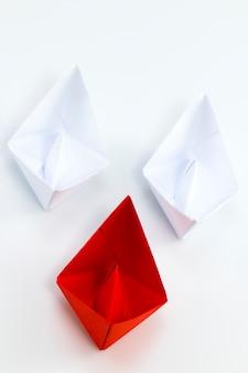 Navire de papier rouge en tête parmi les navires de papier blanc