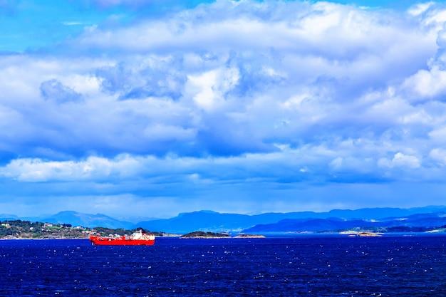 Navire rouge et blanc en mer, les montagnes