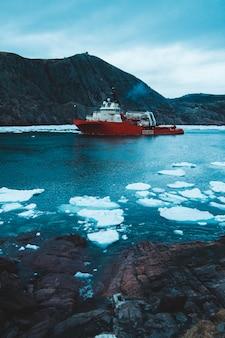 Navire rouge et blanc près des collines