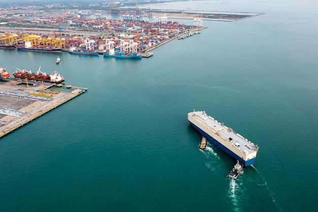 Navire roulier et remorqueur naviguant en mer et quai commercial international porte-conteneurs arrière-plan vue aérienne