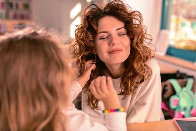 Ne bougez pas. femme incroyable aux cheveux bouclés assis en face de sa fille et gardant le sourire sur son visage
