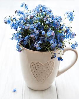 Ne m'oublie pas les fleurs dans une tasse sur la table