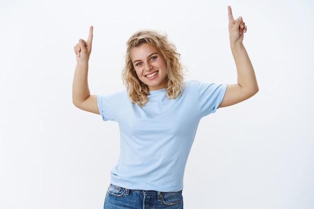 Ne manquez pas la chance et levez les yeux. portrait d'une femme européenne blonde agréable et mignonne avec des yeux bleus et un joli sourire, inclinant la tête souriant joyeusement et levant les mains pour pointer vers le haut à l'espace de copie cool