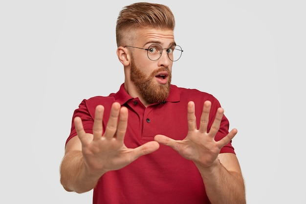 Ne me dérangez pas s'il vous plaît! surpris émotionnel, un jeune homme barbu au gingembre fait un geste d'arrêt, se met les mains en travers, se sent mécontent, porte un t-shirt rouge décontracté, isolé sur un mur blanc.