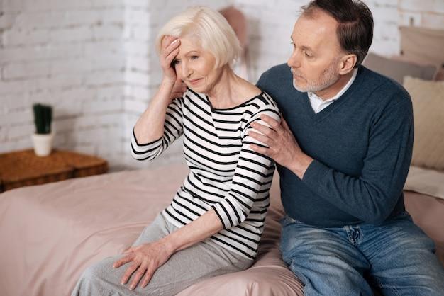Ne panique pas. vieille femme frustrée est assise sur le lit près de son mari et touche son front avec la main.