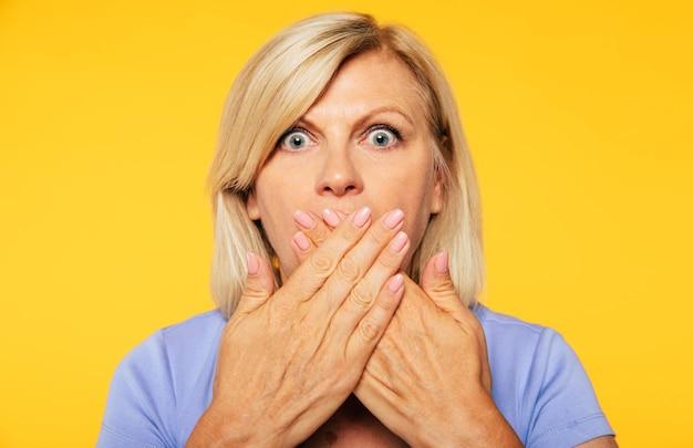 Ne parle pas ! une femme senior blonde se couvre la bouche avec l'aide des mains et regarde la caméra avec un choc dans les yeux