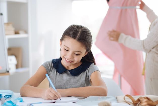 À ne pas oublier. fille créative positive intelligente assise à la table et écrivant dans son cahier tout en notant ses idées créatives