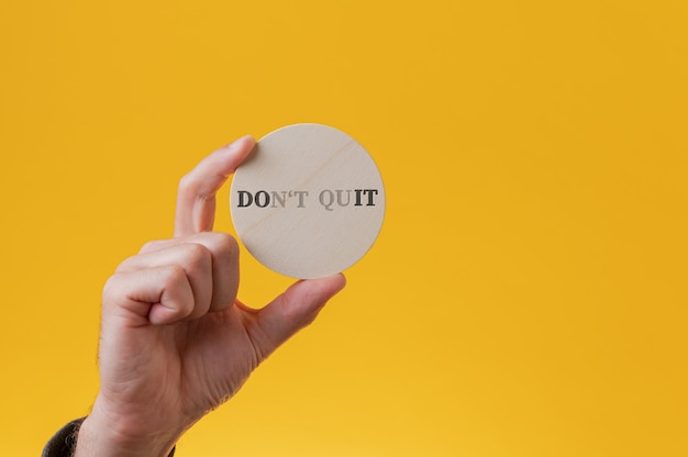 Ne pas quitter le signe épelé sur un cercle de coupe en bois avec quelques lettres disparaissant pour lire un signe do it.