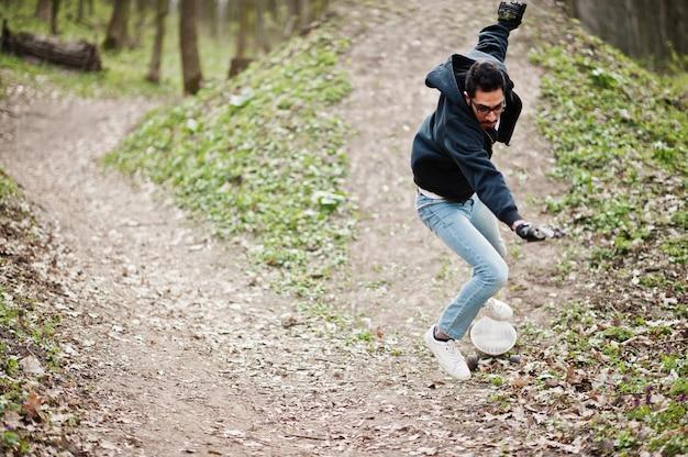 Ne pas tomber d'une planche à roulettes. homme arabe de style rue à lunettes avec longboard sur bois.