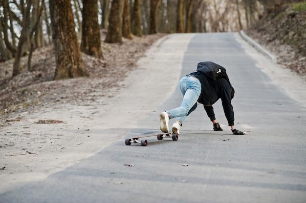 Ne pas tomber d'une planche à roulettes. style arabe homme à lunettes avec longboard longboard sur la route.