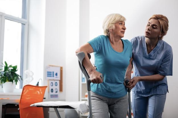 Ne t'en fais pas. belle infirmière agréable debout près de ses patients tout en l'aidant à marcher