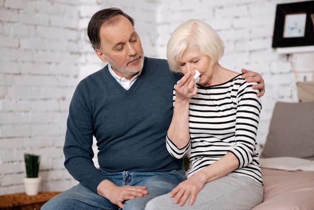 Ne t'en fais pas. senior nice woman pleure près de son mari âgé essayant de lui donner du réconfort.