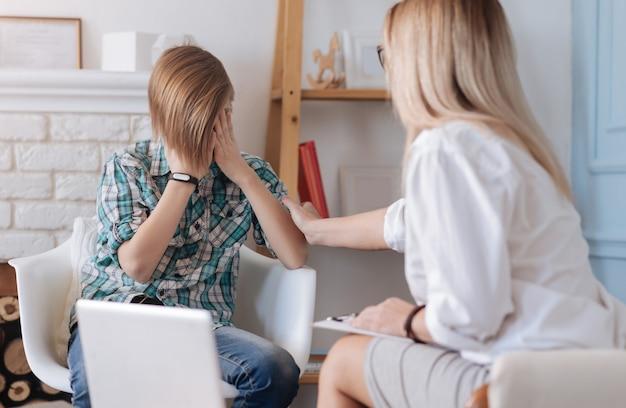 Ne t'inquiète pas. garçon bouleversé avec une coiffure à la mode portant une chemise à carreaux et un jean tenant ses mains sur ses yeux alors qu'il était assis sur une chaise blanche