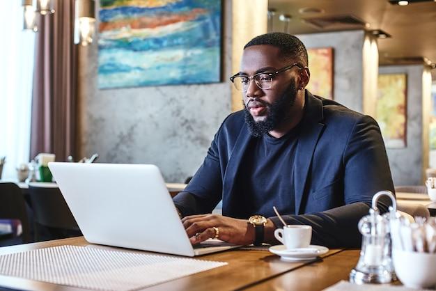 Ne vous plaignez pas et faites de votre mieux, l'homme d'affaires afro-américain travaille avec son ordinateur portable pendant que