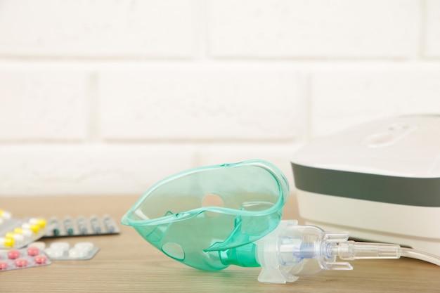 Nébuliseur à compresseur avec masque et pilules sur la table