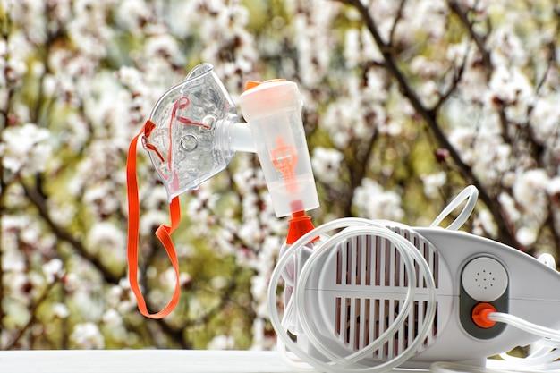 Nébuliseur avec un masque sur un arbre en fleurs.