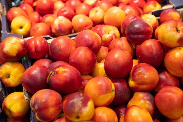 Nectarine colorée délicieusement fraîchement récoltée dans des boîtes en papier au marché fermier de l'épicerie. pour l'agriculture, fond d'illustration alimentaire