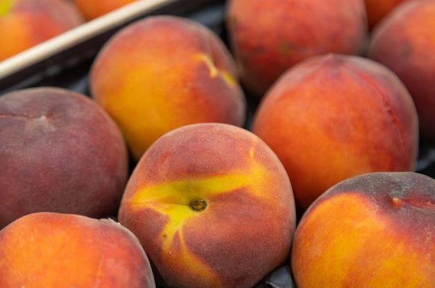 Nectarine mûre parfumée sur le plateau ou la boîte du marché. pour l'illustration de la nourriture, à des fins agricoles
