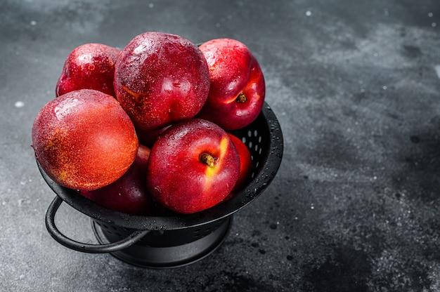 Nectarines biologiques rouges dans une passoire