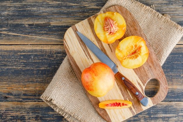 Nectarines avec couteau, planche à découper à plat sur bois et morceau de sac