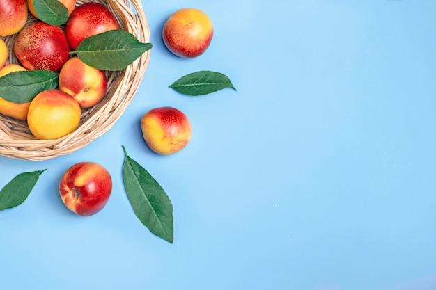 Nectarines fraîchement récoltées se trouve sur fond bleu vitamine végétale kératine naturel
