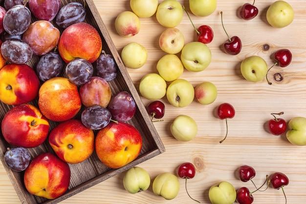 Nectarines et prunes dans une boîte, pêches sur une table.