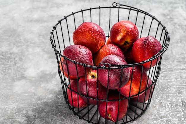 Nectarines rouges fraîches dans un panier en acier. .