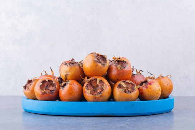 Nèfles brunes dans un plateau bleu sur une surface grise