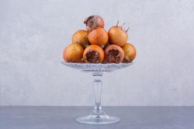 Nèfles brunes dans un support en verre sur une surface grise