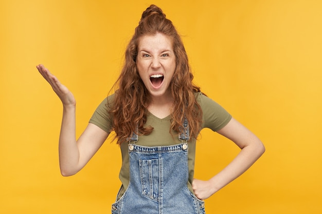 Négative, folle de gingembre, porte une salopette en jean bleu et un t-shirt vert, criant et levant la main avec une expression faciale négative. isolé sur mur jaune