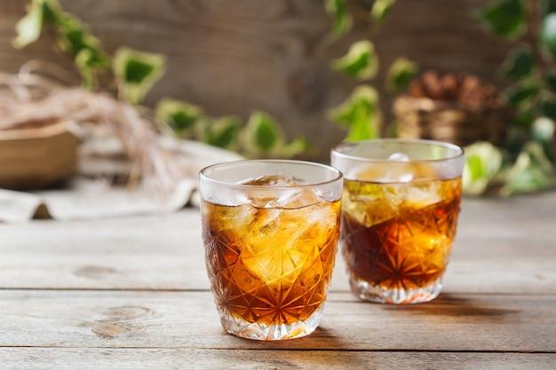 Negroni cocktail italien à l'ancienne avec gin sec, campari, vermouth martini rosso et glace sur une table en bois. boisson rafraîchissante d'été