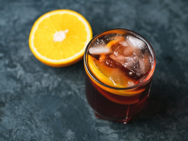 Negroni cocktail à l'orange sur une table en pierre sombre