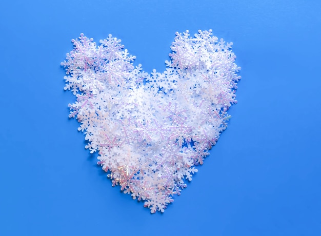 Neige artificielle blanche en forme de coeur sur fond bleu. fond d'hiver.