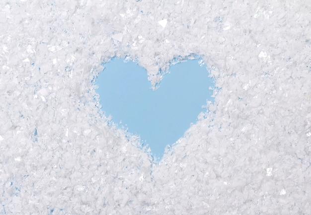 Neige artificielle duveteuse blanche sur table bleue avec coeur