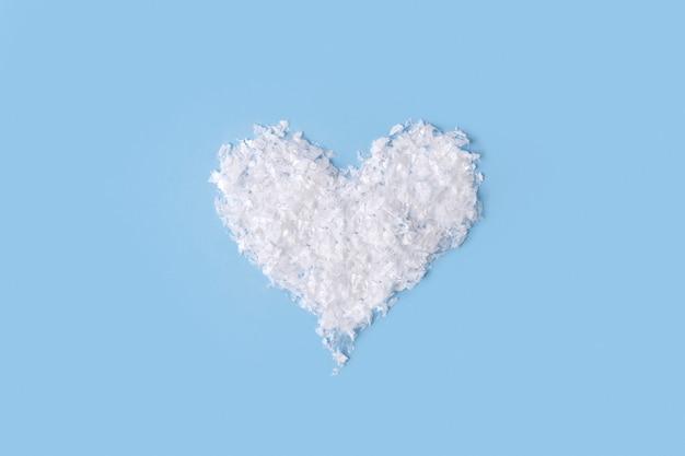 Neige artificielle moelleuse blanche en forme de coeur sur table bleue