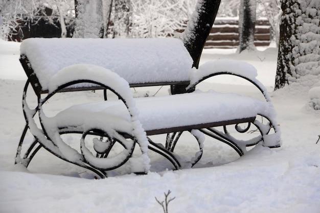 Neige sur banc dans le parc du concept d'hiver