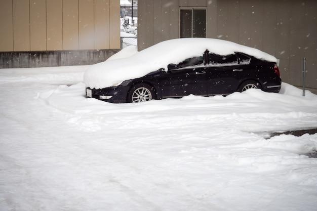 Neige couvrir le toit de la voiture dans le parking. l'hiver.