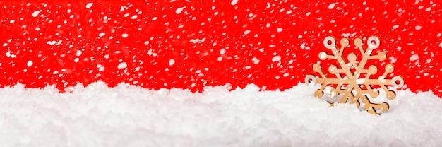 Neige sur fond rouge, chutes de neige ou chutes de neige. grand flocon de neige en bois dans la neige. notion de noël. thème du nouvel an, photo panoramique pour une bannière ou un en-tête de site web. carte de noël.