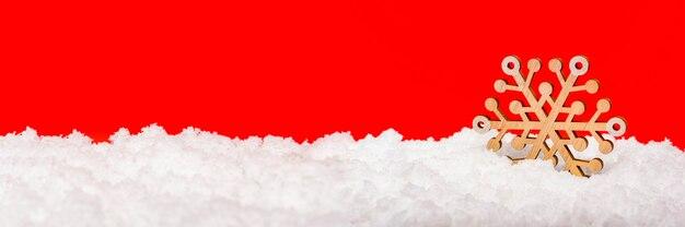Neige sur fond rouge grand flocon de neige en bois dans la neige noël concept nouvel an thème panoram...