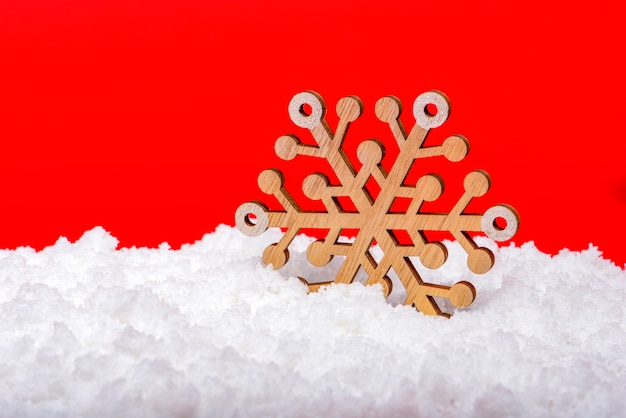 Neige sur fond rouge. grand flocon de neige en bois dans la neige. notion de noël. thème du nouvel an, photo panoramique pour une bannière ou un en-tête de site web. carte de noël pour impression ou design.